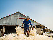 10 FEBRUARY 2016 - BAN LAEM, PHETCHABURI, THAILAND:  Salt field workers empty their baskets of harvested salt in front of a salt barn in Phetchaburi province of Thailand. The salt harvest in Thailand usually starts in February and continues through May. Salt is harvested in many of the provinces along the coast, but the salt fields in Phetchaburi province are considered the most productive. The salt fields are flooded with sea water, which evaporates off leaving salt behind. Salt production relies on dry weather and producers are hoping the current drought will mean a longer harvest season for them.     PHOTO BY JACK KURTZ