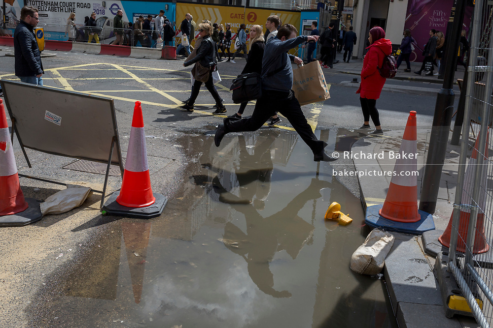 A person jumps over a puddle left in a road on Oxford Street after heavy rain the previous day, on 1st May, in London, England.
