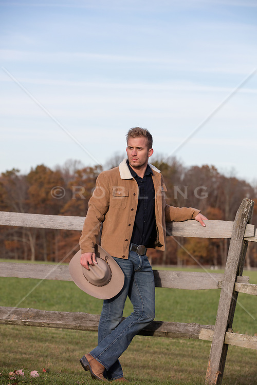 cowboy leaning against a fence