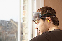 Man wearing goggles and earplugs looking out window