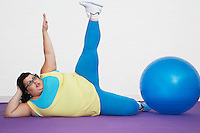 Overweight Woman lying by exercise ball stretching arm and leg upwards