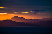 Orange rays of sunrise backlight the Scottish Highlands including Munros (over 3000 feet elevation) in the Fannichs mountain range, seen across the sea from Digg, near Staffin, on Isle of Skye, Scotland, United Kingdom, Europe.