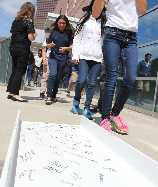 Students at Grady Middle School sign a beam on Monday, May 5, 2015, in celebration of vertical construction on the school's new classroom wing.
