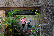 Two children (6 years old, 10 years old) on stairway, viewed through doorway in old sandstone wall. The Rocks, Sydney, Australia
