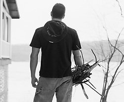 Back of a man holding firewood by a lakehouse