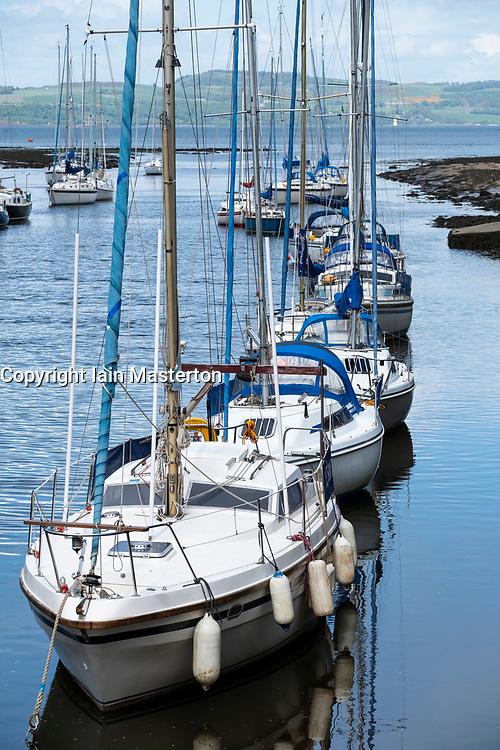 Row of sailing yachts moored on River Almond at Cramond in Edinburgh, Scotland, UK