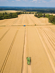 © Licensed to London News Pictures. 23/07/2018. Great Bookham, UK. A combine harvester brings in a crop of milling wheat from bone dry fields on the North Downs on a blistering hot afternoon. Some farmers in the south of England are reporting their earliest wheat harvest in living memory because of the long hot spell.  Forecasters are predicting record temperatures this week. Photo credit: Peter Macdiarmid/LNP