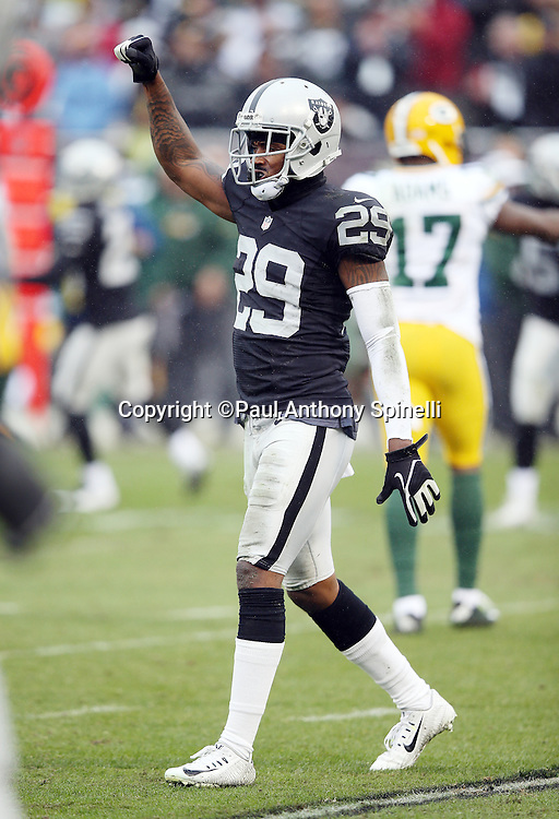 Oakland Raiders cornerback David Amerson (29) signals first down after the Raiders defense gang tackles Green Bay Packers running back James Starks (44) causing a fumble recovered by the Raiders in the second quarter during the 2015 week 15 regular season NFL football game against the Green Bay Packers on Sunday, Dec. 20, 2015 in Oakland, Calif. The Packers won the game 30-20. (©Paul Anthony Spinelli)