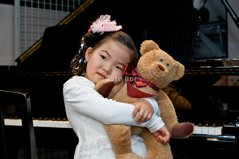 little girl hugging a teddy bear in front of a piano