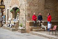 Europe, Italy, Tuscany,San Gimignano, men talking on main square