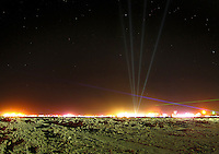 the desert at night lit by lasers and fire