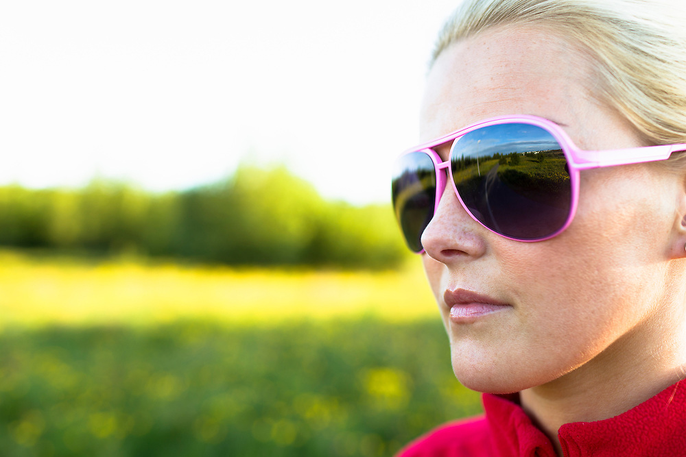 A young woman wearing pink sunglasses