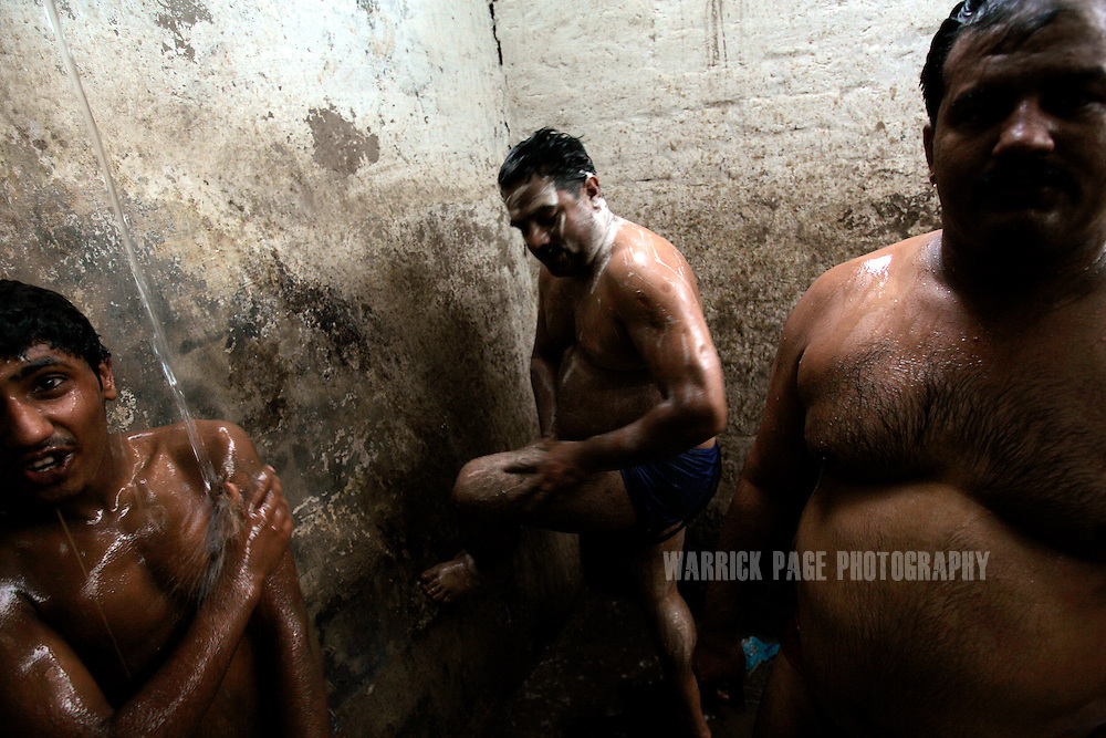 LAHORE, PAKISTAN - JUNE 12: Pehlwanis (wrestlers) shower after a training session, June 12, 2006, in Lahore, Pakistan. Pehlwani is a Persian form of wrestling brought into South Asia by the Mughals, dating back to the 5th century BC but it's popularity is dying in Pakistan due to a lack of funding and interest from the government. Decades ago, hundreds of men would be in constant training, now only dozens remain committed to the ancient sport, attempting to balance daily needs with the strict routine required of a pehlwani. (Photo by Warrick Page)