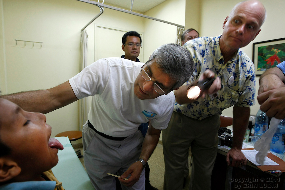 Plastic surgeons Michael Boyajian, of Washington D. C., left, Andreas Doermann, of Milwaukee, WI, look into the mouth of Ruben Quispe, 11, during the screening process at the Hospital Japones in Santa Cruz, Bolivia on Thursday, November 8, 2007, during Operation Smile's World Journey of Smiles...Photograph by Erin Lubin