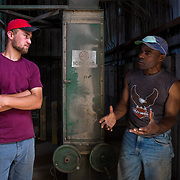 At the Crowell, Texas grain elevator, Juston Wolgemuth, 22, left, a college student and seasonal wheat harvester talks with Michael Lane, 49, a part-time harvest elevator worker and full-time pig farmer. Both of their families have been affected by the fall of the price of wheat. May 2017.