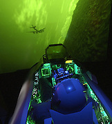 The night sky goes green thanks to a modified F-16 simulator that allows pilots like Capt. Brad Lyons (seated), from Misawa?s 14th Fighter Squadron, to fly improved night vision goggle training missions. John McDonald (not seen) used a ?common sense, bailing wire and bubble gum? approach to crafting the changes after a contractor said converting the simulators for the missions would cost $3 million. .