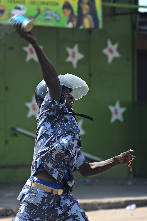 LOME, TOGO - 12-10-05   - A Gendarme throws a tear gas canister. Protesters clashed with police in Lomé on October 5. A peaceful protest was scheduled by opposition groups, but their route was blocked by police.  For months, opposition parties have been calling for the departure of president Faure Gnassingbe, whose family has been in power for over 40 years.   Photo by Daniel Hayduk