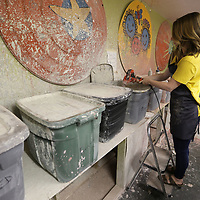 Alaina Brown has to use s tep ladder and a power drill with a mixer attached to stir up the underglaze before she begin glazing the freshly fired pottery called bisque.