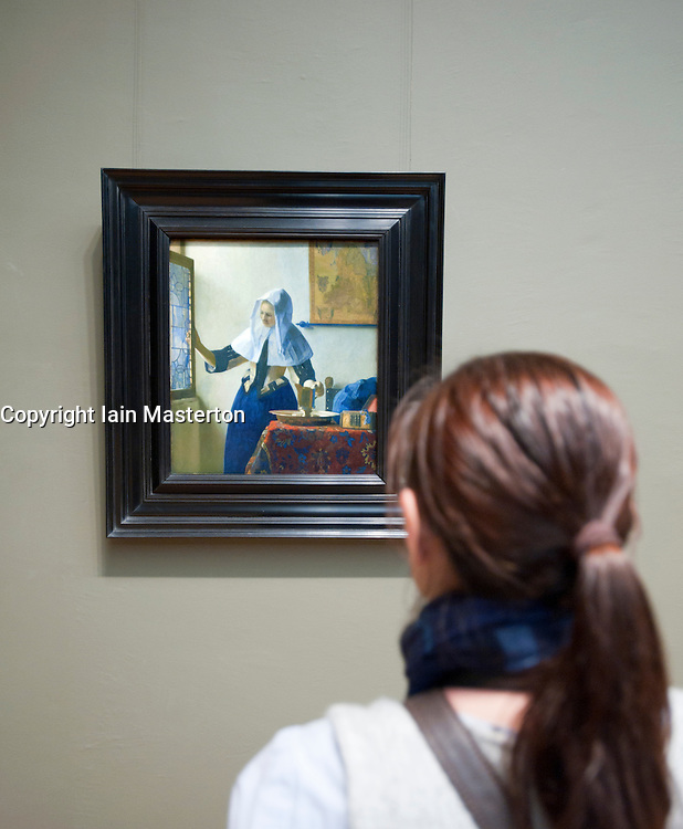 Woman looking at painting by Vermeer at Metropolitan Museum of Art in Manhattan , New York City, USA