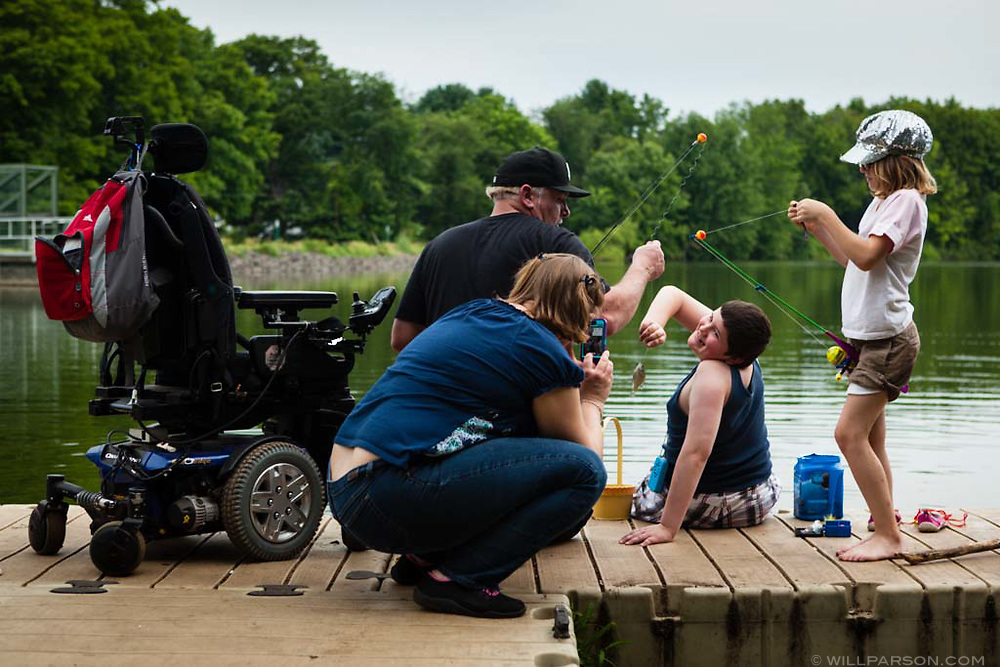 """James Freeman, 9, aided by his father Don Freeman of Southington, holds up a his catch so his mother Lisa Klee can take a picture, while James' sister Emilee Hinton, 9, adjusts the bait on her line at Crescent Lake in Southington, Conn., on July 28, 2013. James and his brother Jesse Freeman, 10, have Duchenne muscular dystrophy and used their motorized wheelchairs to reach the lake. """"I love this dock because you can drive right out,"""" said Brian Hinton, the boys' stepfather. Photograph by Will Parson   wparson@courant.com"""