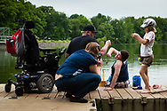 "James Freeman, 9, aided by his father Don Freeman of Southington, holds up a his catch so his mother Lisa Klee can take a picture, while James' sister Emilee Hinton, 9, adjusts the bait on her line at Crescent Lake in Southington, Conn., on July 28, 2013. James and his brother Jesse Freeman, 10, have Duchenne muscular dystrophy and used their motorized wheelchairs to reach the lake. ""I love this dock because you can drive right out,"" said Brian Hinton, the boys' stepfather. Photograph by Will Parson 