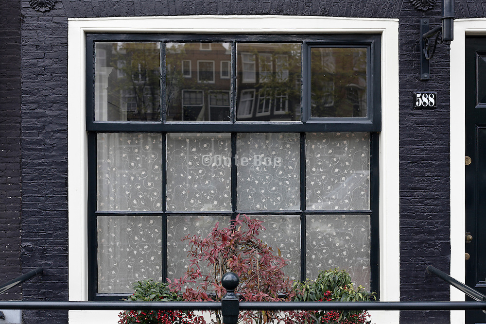 Amsterdam Holland canal house window with traditional grachten houses roofs reflection