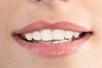 studio shot close up detail of the face of a beautiful young women with perfect lips mouth and teeth smiling