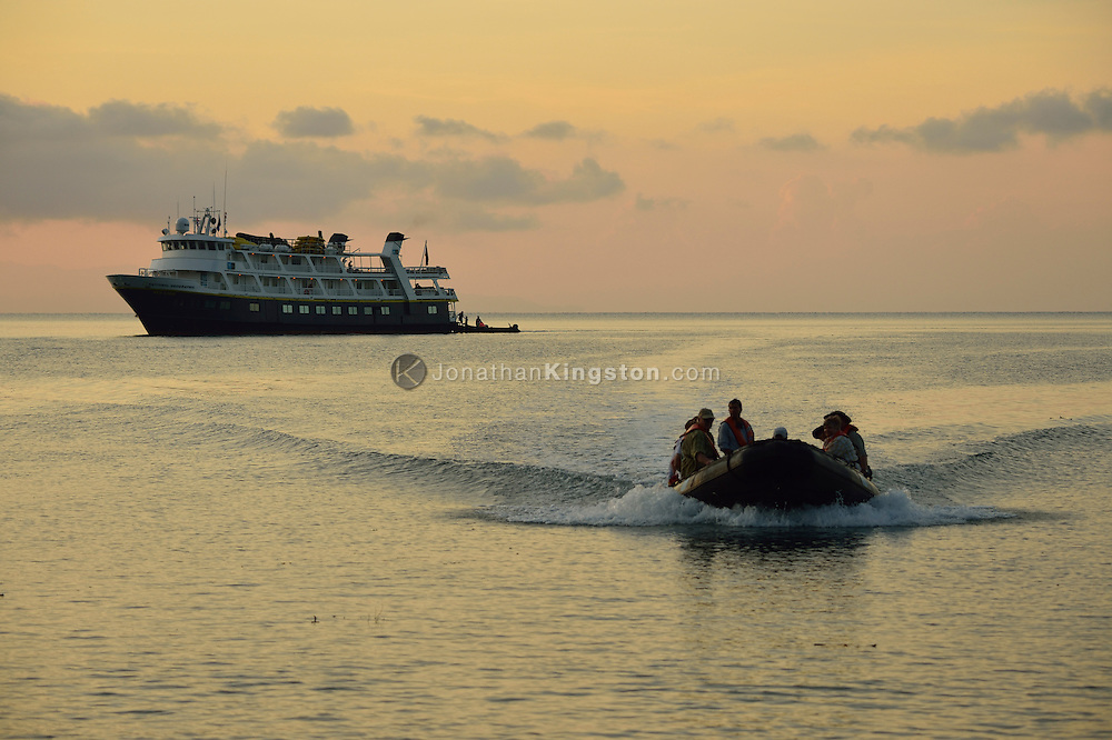 Tourists ride in a small inflatable boat at sunrise in the waters of Golfo Dulce, or Sweet Gulf, Puntarenas, Costa Rica.