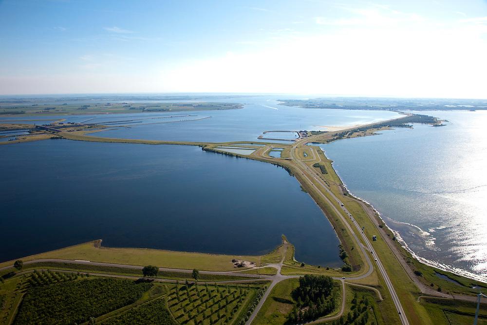 Nederland, Zeeland, Grevelingen, 12-06-2009; Grevelingendam naar Bruinisse op Duiveland (aan de horizon), naar links de Philipsdam naar St. Philipsland met de Krammersluizen. De sluizen maken scheepvaartverkeer naar de Oosterschelde (aan de verre horizon) mogelijk. Rechts de Grevelingen of Grevelingenmeer, het grootste zoutwatermeer van Europa, ontstaan door het afsluiten van de zeearm door de Brouwersdam in het kader van de Deltatwerken  (1971). Door het verdwijnen van het getij is de ecologische kwaliteit van het water steeds verder achteruitgegaan, er zijn initiatieven om een opening in de Brouwersdam te maken om zo het getij deels terug te laten keren. <br /> Grevelingen with sweet water lake, the result of closing the connection to the North Sea. This closure has caused numerous ecological problems<br /> Aerial photo (additional fee required). Luchtfoto (toeslag).<br /> foto Siebe Swart / photo Siebe Swart