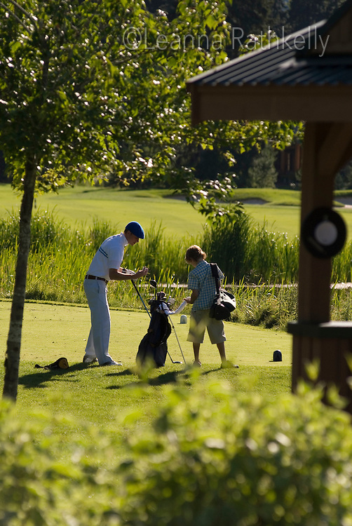 A dad and son walk the Nicklaus North golf course in late summer, located in Whistler, BC Canada.