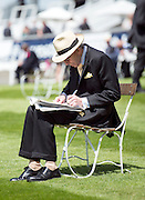 TODAY PICTURE © Licensed to London News Pictures. 06/06/2014. Epsom, UK. A man reads the Racing Post.  Ladies Day today 6th June 2014 at Epsom 2014 Investic Derby Festival in Surrey. Traditionally, elegant, fashionable racegoers gather for a classic day's racing at Epsom Racecourse, Surrey. Photo credit : Stephen Simpson/LNP
