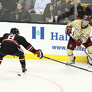 Michael Sit #18 of the Boston College Eagles passes the puck past Adam Reid #8 of the Northeastern Huskies during The Beanpot Championship Game at TD Garden on February 10, 2014 in Boston, Massachusetts. (Photo by Elan Kawesch)