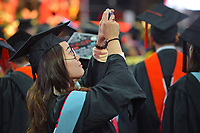 Graduate takes a photo after walking into PNC Arena for 2017 Spring Commencement.