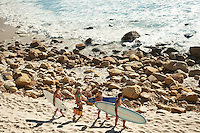 Young people carrying surfboards along beach