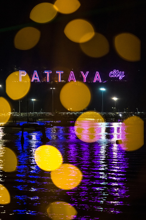 A neon lit sign for Pattaya City on display over the water in Pattaya, Thailand.