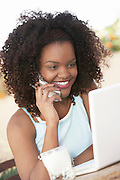 Young Woman Using Cell Phone and Laptop