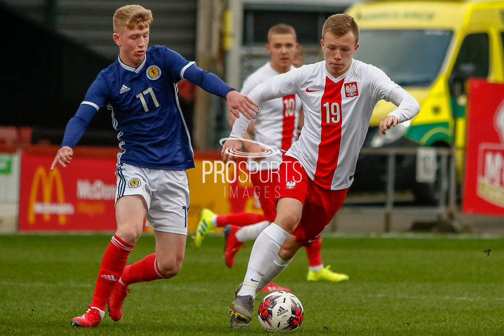 Poland's Daniel Dudzinski on the ball under pressure form Scotland's Stuart Mckinstry (Motherwell) during the U17 European Championships match between Scotland and Poland at Firhill Stadium, Maryhill, Scotland on 26 March 2019.
