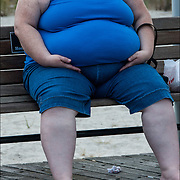 Close up of very obese Caucasian woman siting on broadwalk bench.  Obesity in America