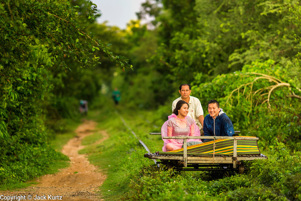 29 JUNE 2013 - BATTAMBANG, CAMBODIA:  People ride the Bamboo Train from O Sra Lav, a small village southeast of Battambang, to the terminal station near Battambang. The bamboo train, called a norry (nori) in Khmer is a 3m-long wood frame, covered lengthwise with slats made of ultra-light bamboo, that rests on two barbell-like bogies, the aft one connected by fan belts to a 6HP gasoline engine. The train runs on tracks originally laid by the French when Cambodia was a French colony. Years of war and neglect have made the tracks unsafe for regular trains.  Cambodians put 10 or 15 people on each one or up to three tonnes of rice and supplies. They cruise at about 15km/h. The Bamboo Train is very popular with tourists and now most of the trains around Battambang will only take tourists, who will pay a lot more than Cambodians can, to ride the train.       PHOTO BY JACK KURTZ
