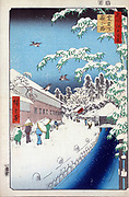 Atagoshita and Yabu Lane: 1857. Utagawa Hiroshige (1797-1858) Japanese Ukiyo-e artist 'One Hundred Famous View s of Edo' (Tokyo).  Pedestrians in falling snow, Mount Atago right background, Bamboo right foreground. Winter Sparrow