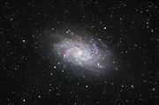 """Die Galaxie M 33 befindet sich im Sternbild Dreieck und ist das drittgrösste Mitglied der Lokalen Gruppe. Über die Längsachse gemessen ist die Galaxie etwa 60.000 Lichtjahre gross und zwischen 2.4 Mio. und 3.6 Mio. Lichtjahren von uns entfernt. Die Galaxie bewegt sich mit einer Geschwindigkeit von etwa 200 km/s auf uns zu und gleichzeitig mit 68 km/s vom Zentrum der Lokalen Gruppe weg. Von der Erde aus blicken wir unter einem Winkel von 54 Grad auf die Galaxienscheibe. Dank der """"Nähe"""" und der guten Lage zu uns können in dieser Galaxie eine Menge extragalaktischer Deep-Sky Objekte erkannt werden, davon alleine in den Spiralarmen ca. 80 Emissionsnebel. Aufnahmedaten Triangulum Galaxie Messier 33, NGC 598: Luminanz: 10 x 480 s @ 800ASA Aufnahmeoptik: Takahashi FS102 NSV f/8 Montierung: Losmandy G11 + Littlefoot Kamera: Canon EOS 20Da Autoguiding: Webcam guiding @ Vixen ED81 + 2x barlow Bildbearbeitung: ImagesPlus, PS, Neat Image"""