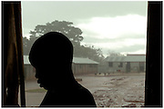 Bea Ahbeck/Fremont Argus<br /> <br /> A former child soldier is silhouetted against a sudden downpour at the GUSCO (Gulu Support the Children Organization) Child Soldier Rehabilitaion Center in Gulu, Northern Uganda, Friday, October 28, 2005. Joseph Kony's rebel army LRA (Lord's Resistance Army) have abducted over 20,000 children in the last 18 years of war and turned them into child soldiers, porters or sex slaves. The center has rehabilitated over 2,300 children since its' foudation in 1994 following the abduction of 130 girls from Aboke School in Apac, Northern Uganda in 1996.