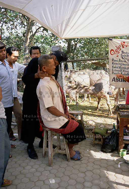 Indonesia, Java island : the Dukun (healer) Pak Iwo blows the ear of an old man to heal his pain.<br /> Indonesia, Giava: il dukun (guaritore) Pak Iwo soffia sul  suo paziente per guarirlo dai dolori.