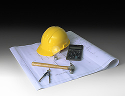 hard hat, blueprints, hammer, calculator, calipher on gradientdark background