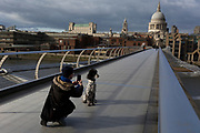 As the UK government announces further Coronavirus-related restrictions to its citizens, with the immediate closure of pubs, cafes, gyms and cinemas, and the worldwide number of deaths reaching 10,000 with 240,000 cases, 953 of those in London alone, dog walker 'Dan' photographs his client's poodle with a background of St. Paul's Cathedral at the end of an unusually quiet Millennium Bridge, on 20th March 2020, in London, England.