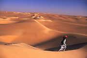 A Bedouin desert guide, Achmed Abu Bakr strides across a massive dune ridge. It is this ridge and many others like it that comprise the Great Sand Sea, just south of the Siwa Oasis. Egyptian Western Desert or Lybian Desert.
