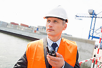 Middle-aged man using walkie-talkie in shipping yard