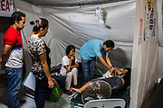 Nurse Sharon Pacaldo (2nd from left), of Philippine Red Cross, looks on as a doctor checks on a severely dehydrated baby in the medical tent for evacuees in the city's largest stadium in Zamboanga, Mindanao, The Philippines on November 4, 2013. These Internally Displaced People (IDP) had taken refuge in this stadium after surviving the 3 week long attack by MNLF rebels. Photo by Suzanne Lee for SPRINT-IPPF