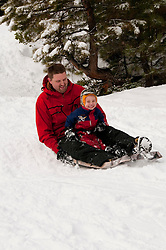 California, Lake Tahoe: Child and father enjoy snow play with sled at North Lake Tahoe Regional Park.  Photo copyright Lee Foster.  Photo # cataho107643