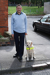 Guide Dog in harness, at kerb with owner